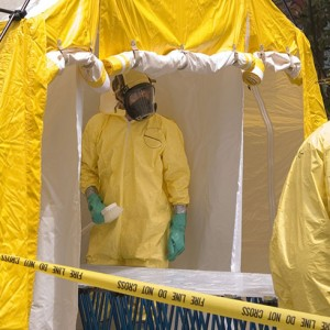 Image of a technician in a tyvek suite preparing to perform soil remediation.