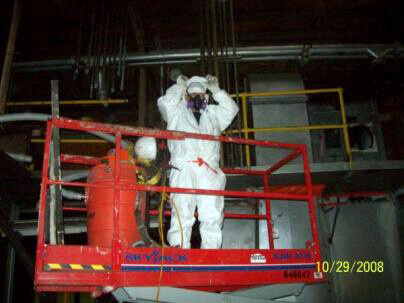 Image of two One Stop Environmental employees removing asbestos from the Chicago Bridge building.