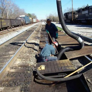 Image of two One Stop Environmental employees using a vacuum truck to remove hazardous waste for Norfolk Southern Railroad.