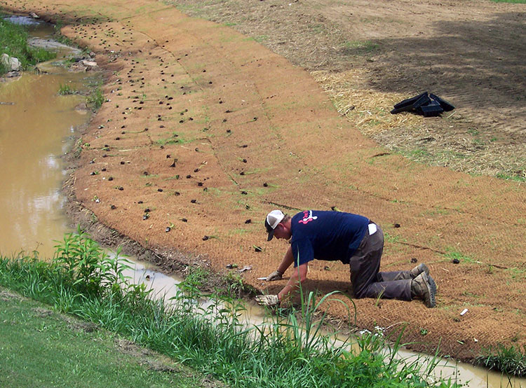 Image of a One Stop Environmental employee working a stream restoration project for Timberline Golf Course.