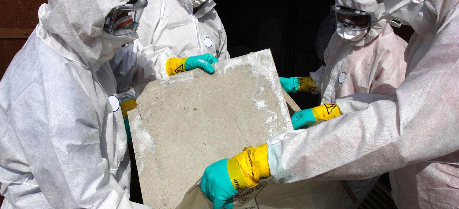 Image of technicians in tyvek suits performing asbestos abatement