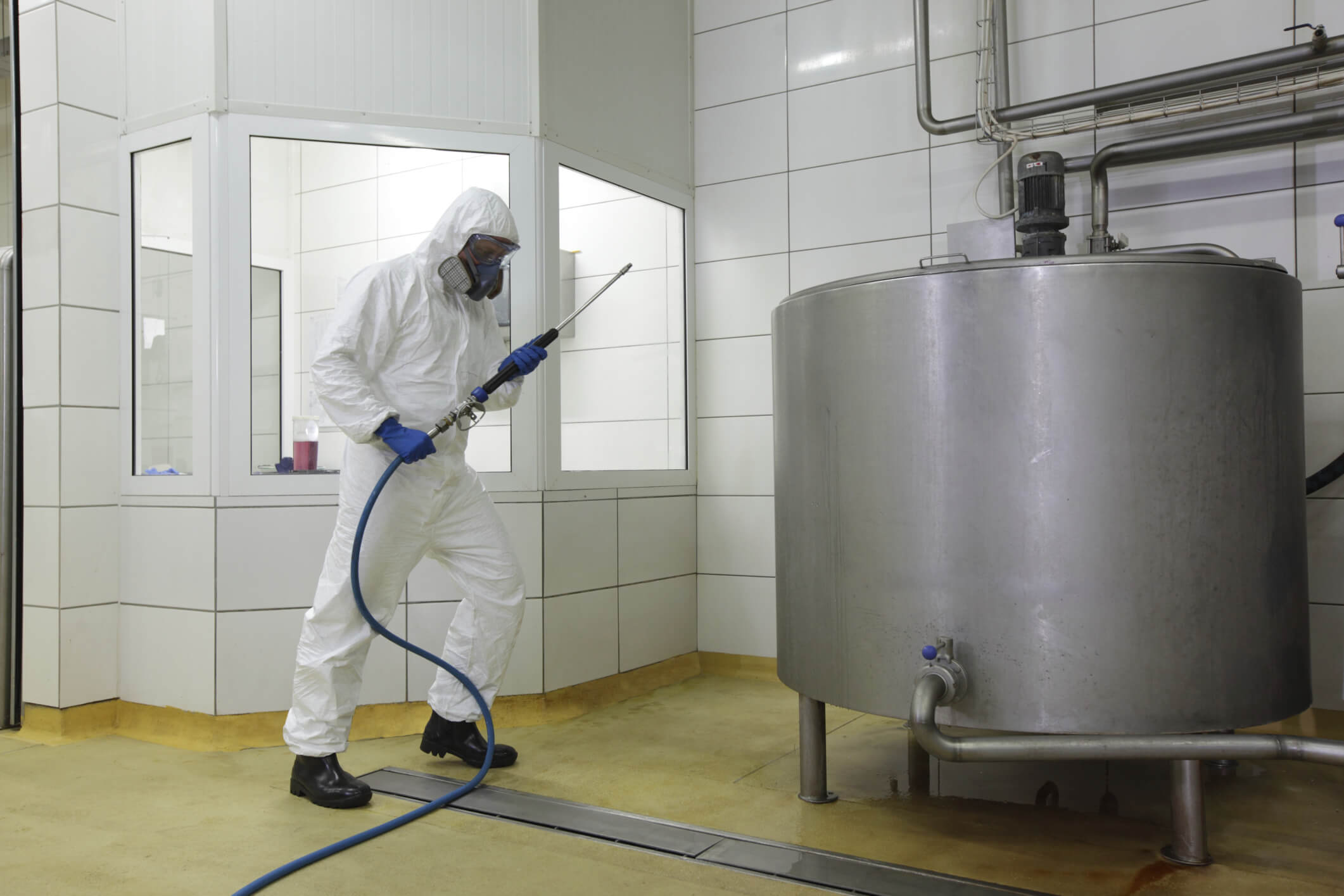 Image of a technician performing pressure cleaning in an industrial facility